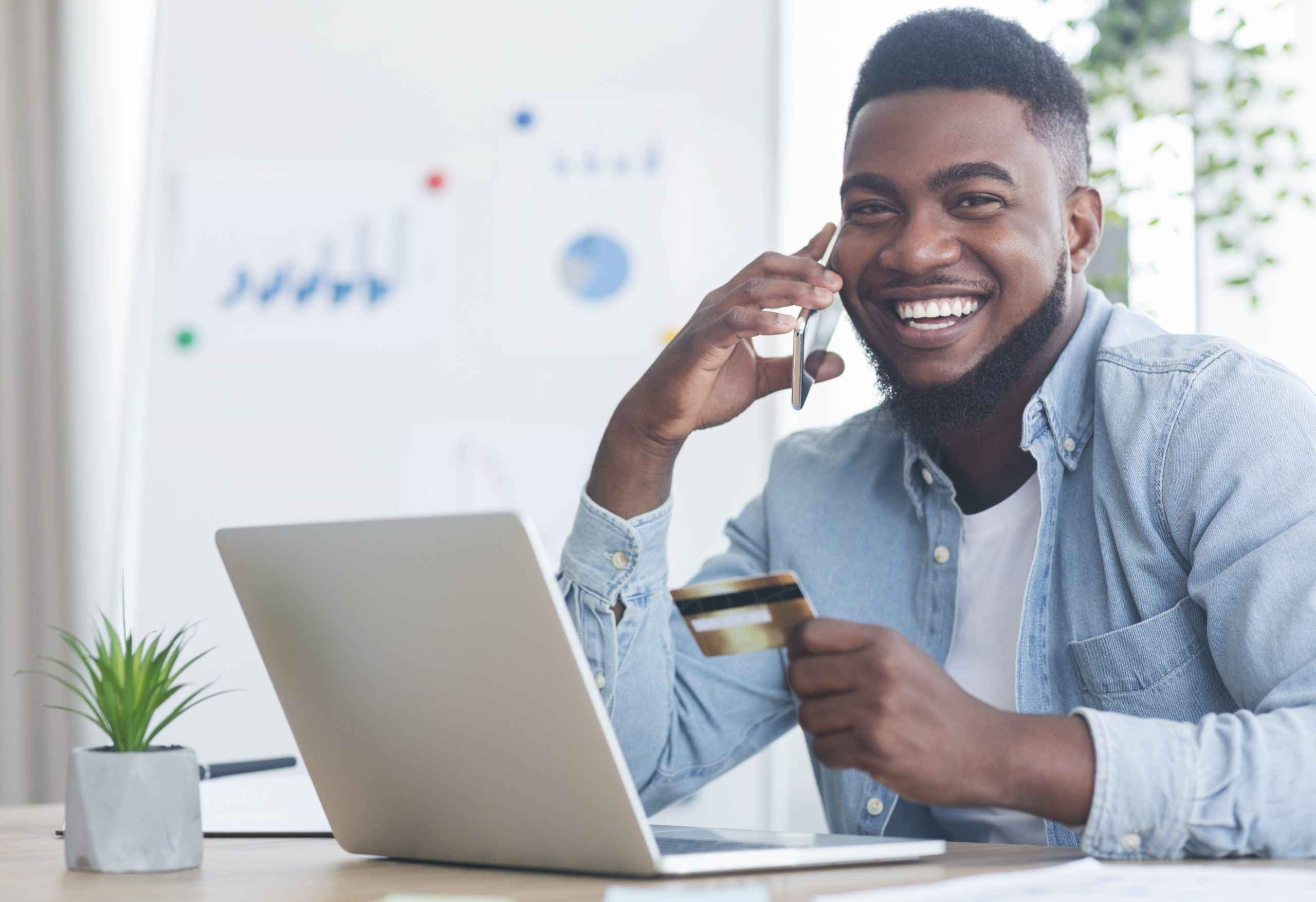 cheerful black guy talking on phone and holding cr UKL26JX scaled