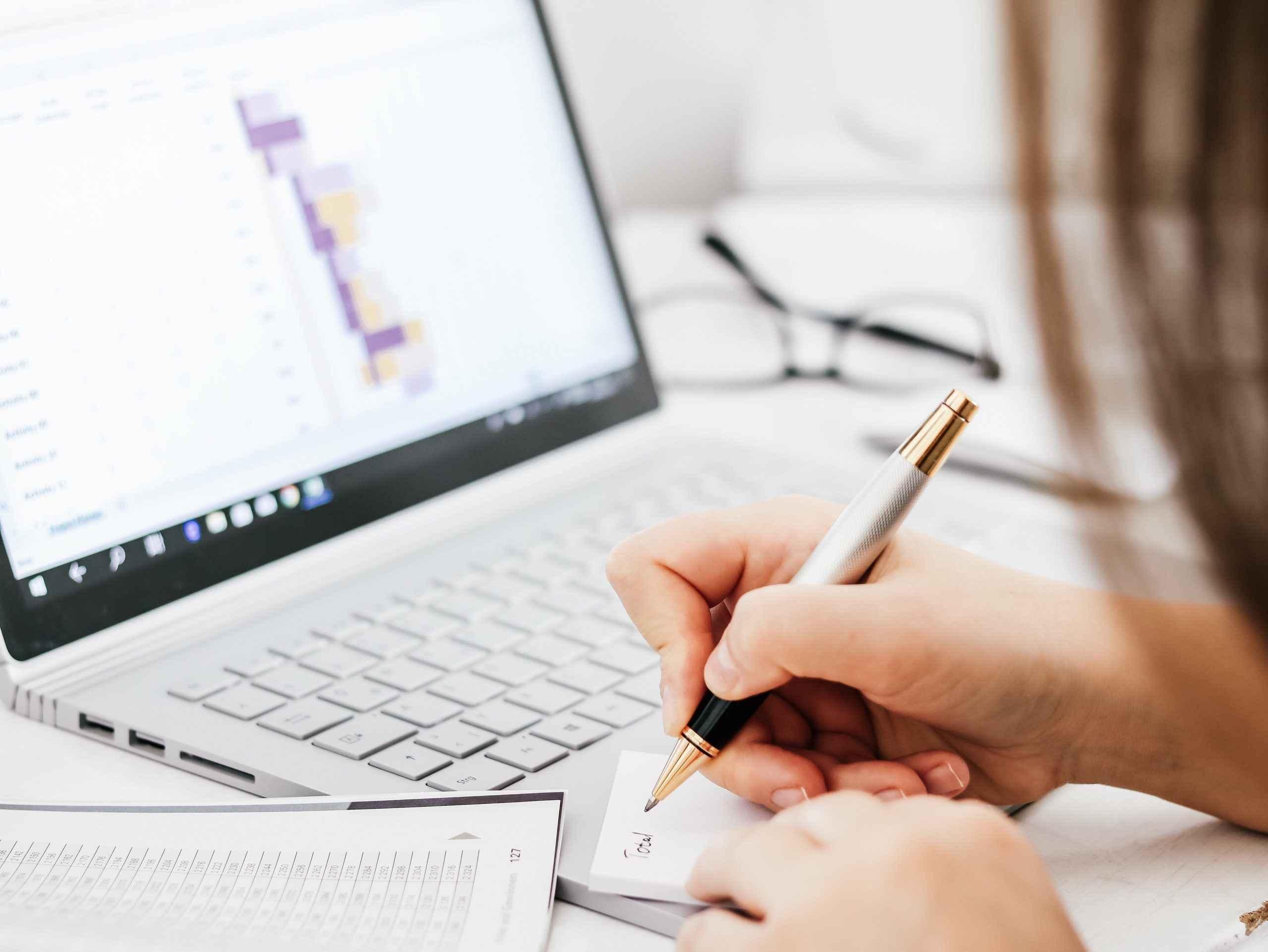 woman writing laptop keyboard graph profit and los J79NQJM scaled